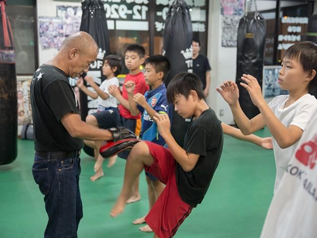 トレーナーは蹴り運動をしている少年男子生徒達を監督している